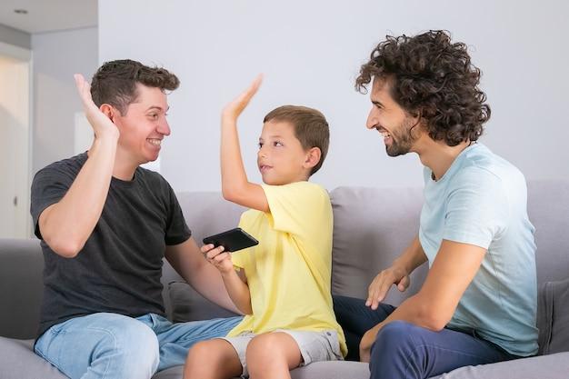 Garoto feliz com smartphone dando mais cinco a dois pais alegres. pais e filho jogando juntos no celular. família em casa e conceito de pais gays Foto gratuita