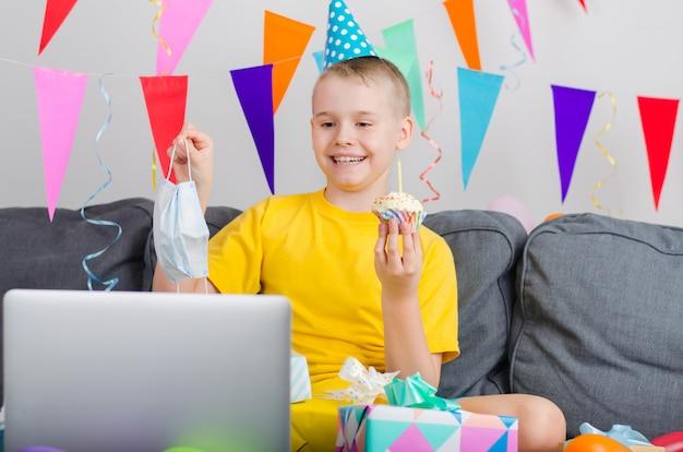 Garoto feliz em máscara facial de medicina comemora aniversário por chamada de vídeo para laptop Foto Premium
