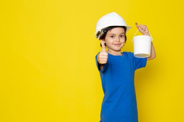 Garoto feliz sorrindo adorável adorável segurando tintas de camiseta azul na parede amarela Foto gratuita