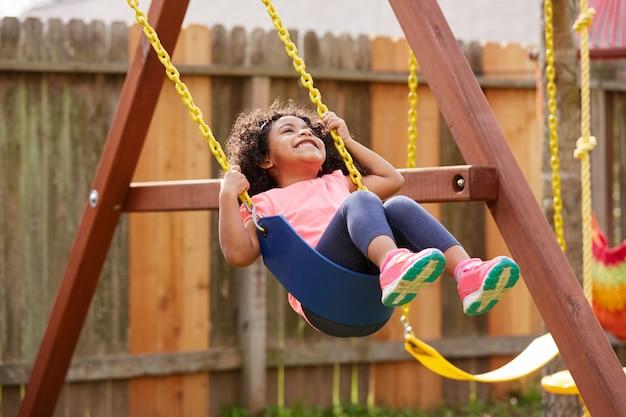 Garoto garota da criança balançando em um balanço de recreio Foto Premium