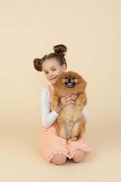 Garoto garota sentada e segurando o cão spitz Foto Premium