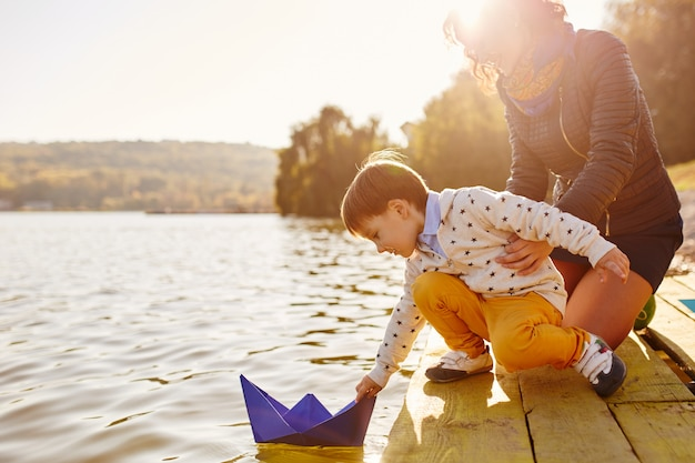 Garoto jogando com navio de papel de brinquedo à beira do lago Foto gratuita
