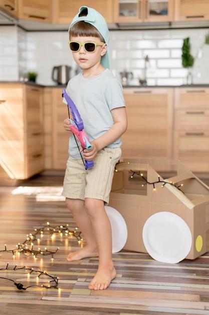 Garoto legal de tiro completo segurando o brinquedo de arco Foto gratuita