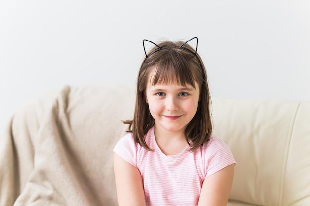 Garoto linda garota com orelhas de gato sentado no sofá. crianças e conceito de infância. Foto Premium