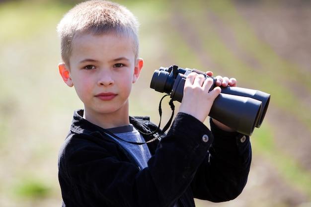 Garoto loiro bonito olhando através de binóculos na distância no fundo desfocado Foto Premium