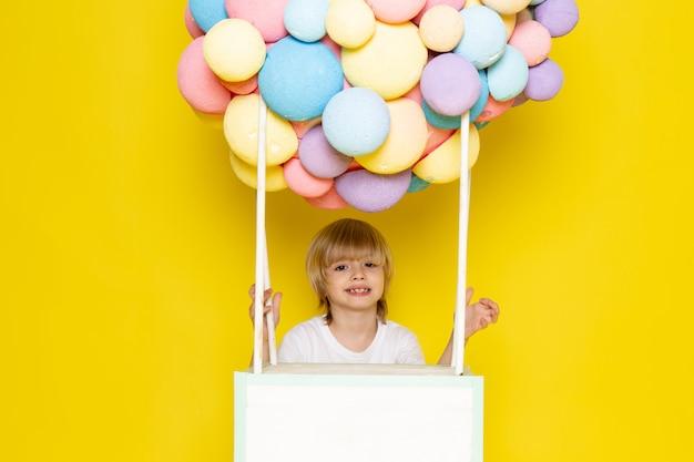 Garoto loiro vista frontal em camiseta branca, juntamente com balões de ar coloridos no amarelo Foto gratuita