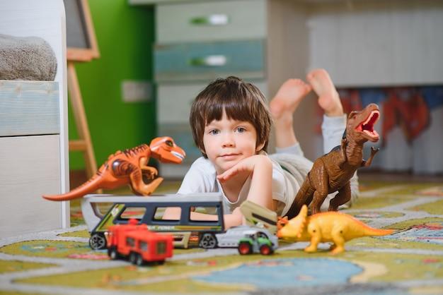Garoto menino bonitinho brincando com muitos carros de brinquedo internos. pré-escolar feliz se divertindo em casa ou no berçário Foto Premium