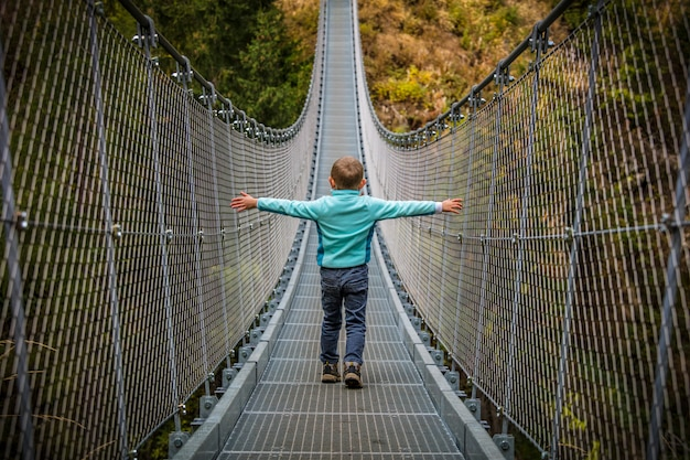 Garoto na ponte suspensa Foto Premium