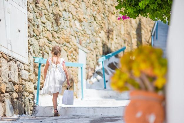 Garoto na rua da aldeia tradicional grega típica com escadas brancas na ilha grega Foto Premium