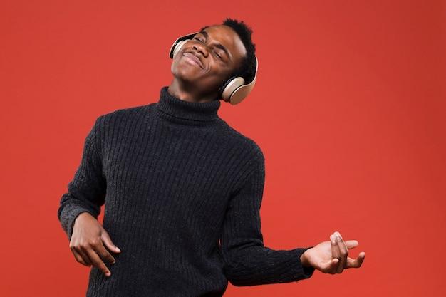 Garoto negro posando com fones de ouvido Foto gratuita