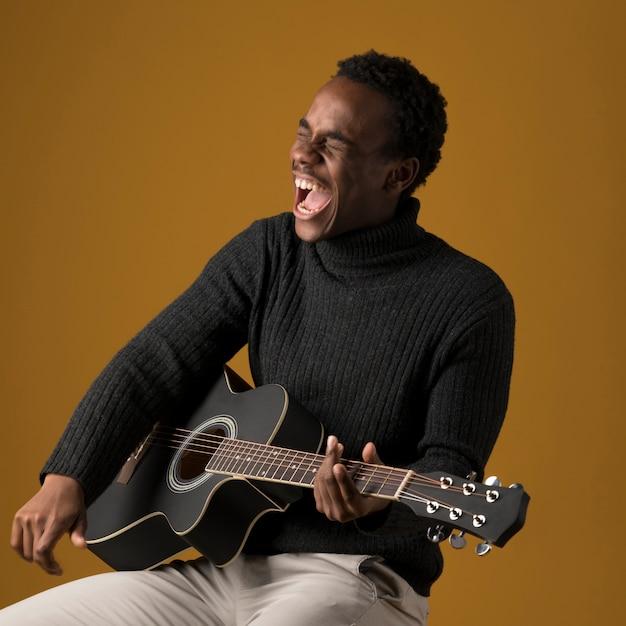 Garoto negro tocando guitarra Foto gratuita