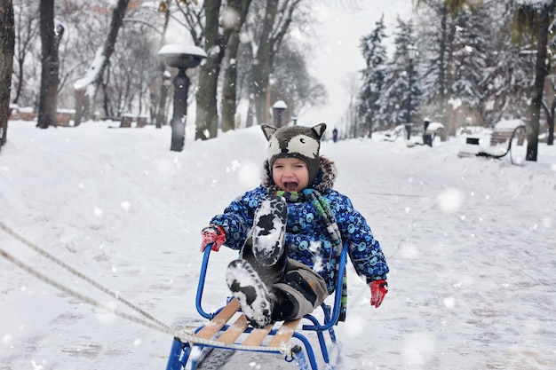 Garoto no trenó no parque de inverno Foto Premium