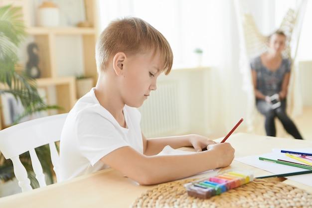 Garoto ocupado de idade pré-adolescente sentado em casa com plasticina colorida na mesa de madeira, usando lápis, concentrado no processo criativo. imagem horizontal de um pequeno artista caucasiano pintando, fazendo lição de casa Foto gratuita