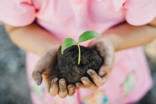 Garoto plantando uma árvore para o conceito do dia da mãe terra. Foto Premium