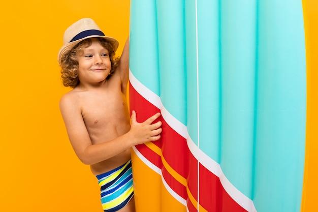 Garoto ruivo feliz com um chapéu de verão, um colchão de ar sobre fundo amarelo Foto Premium