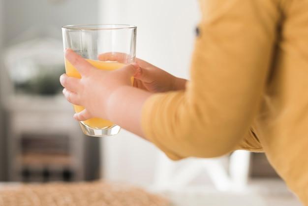 Garoto segurando copo de suco de laranja Foto gratuita