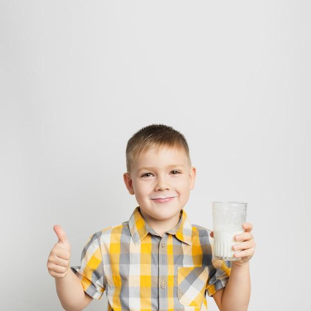 Garoto segurando o copo de leite na mão Foto gratuita