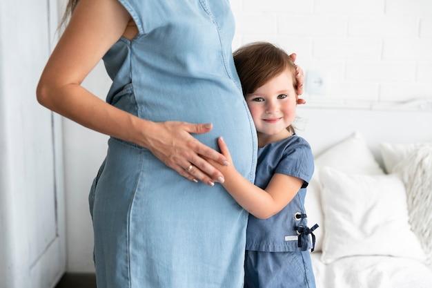 Garoto sorridente, abraçando sua mãe grávida Foto Premium