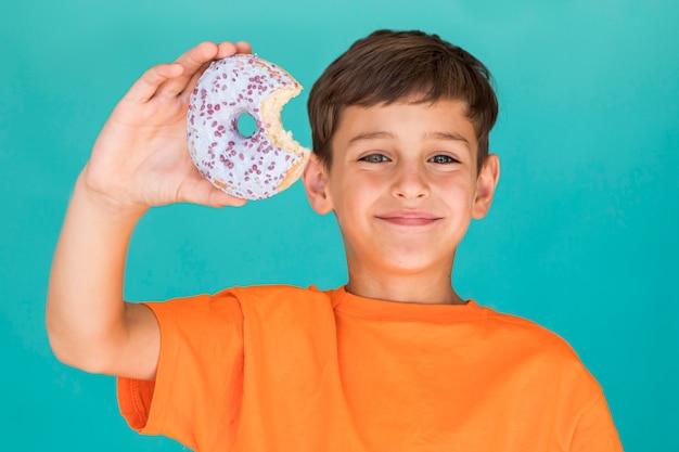Garoto sorridente segurando um donut de vidro Foto gratuita