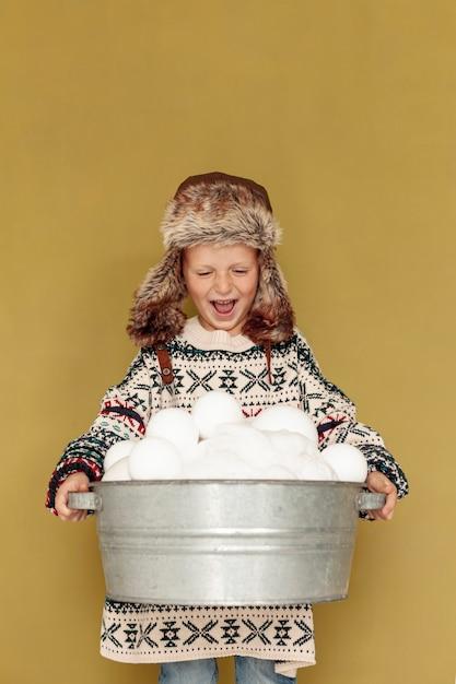 Garoto sorridente vista frontal com chapéu e bolas de neve Foto gratuita