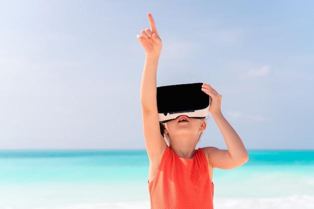 Garoto usando óculos de realidade virtual na praia Foto Premium