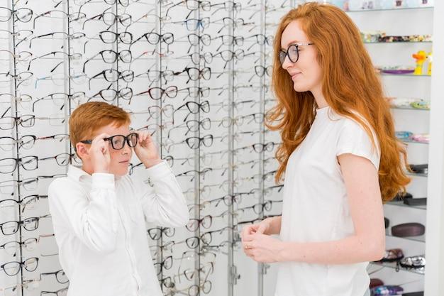 Garoto usando óculos na frente de sua jovem irmã na loja de óptica Foto gratuita