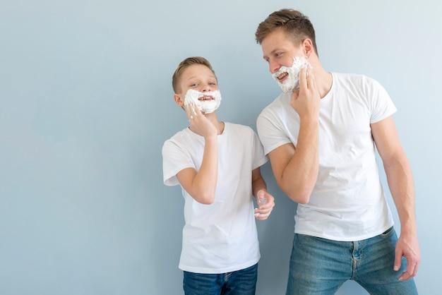 Garotos de vista frontal usando espuma de barbear Foto gratuita