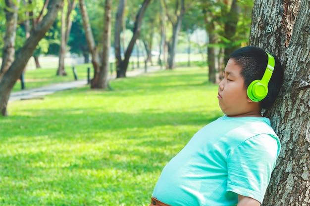 Garotos usando fones de ouvido de música verde de pé contra a árvore, olhos fechados, feliz Foto Premium