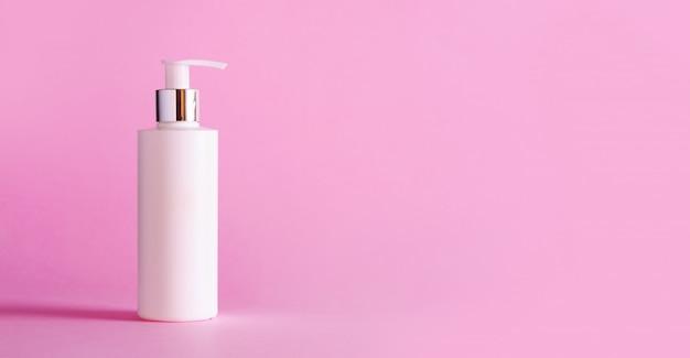 Garrafa branca de loção hidratante no fundo rosa com espaço de cópia Foto Premium
