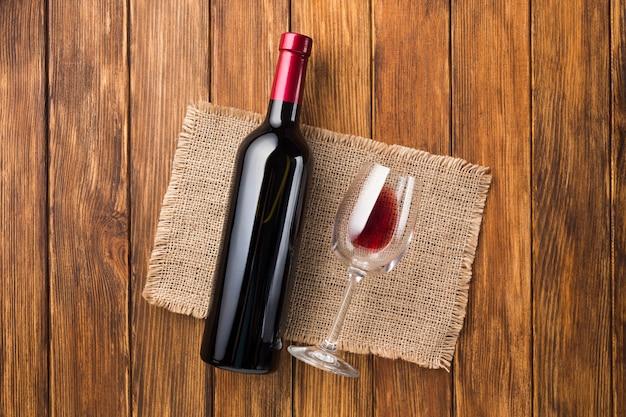 Garrafa cheia de vinho tinto e copo vazio Foto gratuita