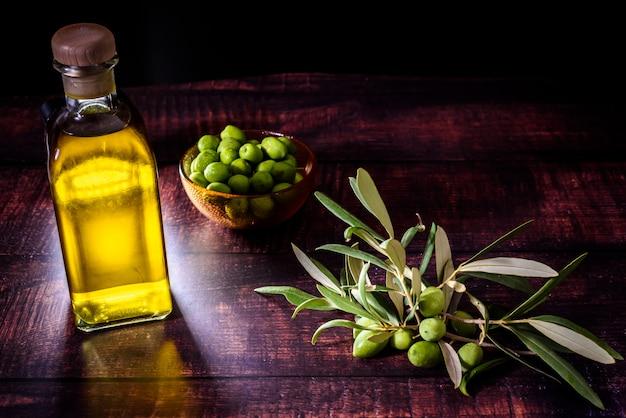 Vidro de azeite ao lado de um buquê de azeitonas cruas