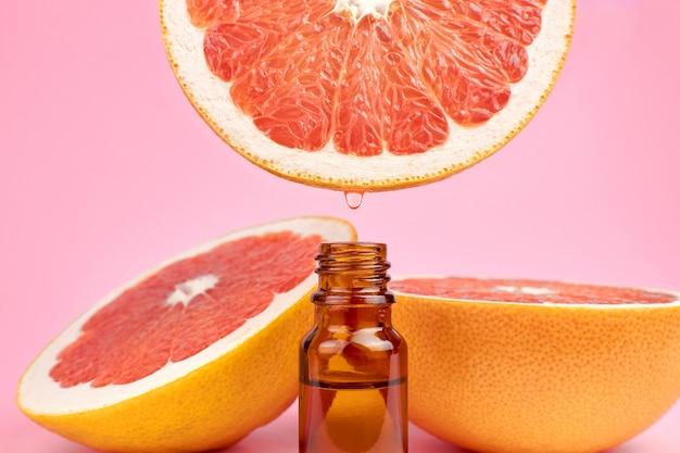 Garrafa com óleo cítrico essencial e toranjas vermelhas frescas Foto Premium