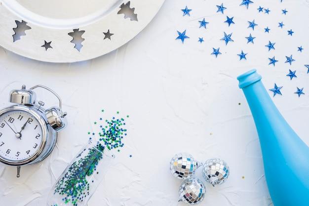 Garrafa com relógio e lantejoulas na mesa Foto gratuita