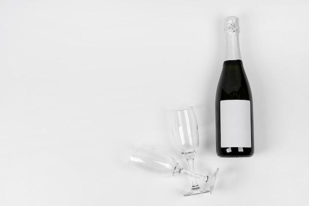 Garrafa com vista superior e copos com cópia-espaço Foto gratuita