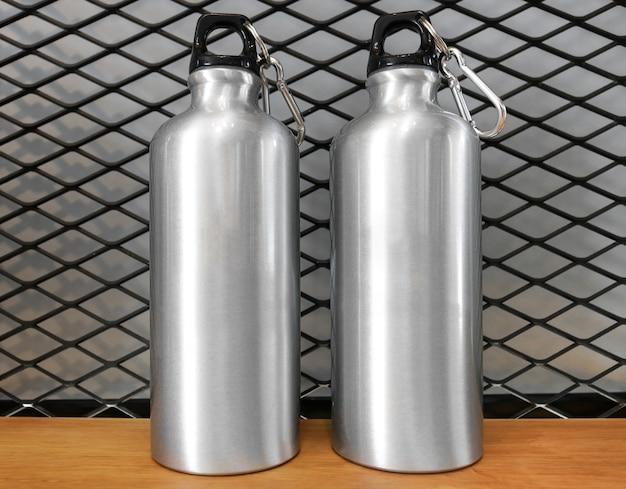 Garrafa de água e carabiner metálicos no fundo de madeira da prateleira. Foto Premium