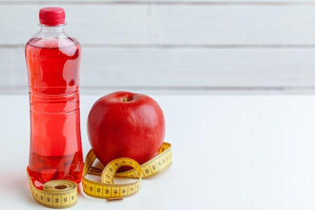 Garrafa de água, fita métrica e maçã fresca em cima da mesa Foto Premium