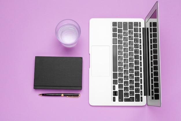 Garrafa de água na mesa de escritório perto de laptop Foto Premium