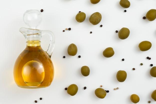 Garrafa de azeite com azeitonas ao lado Foto gratuita