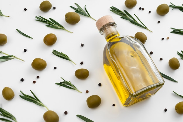 Garrafa de azeite com azeitonas e folhas ao redor Foto gratuita