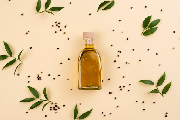 Garrafa de azeite rodeada de folhas de oliveira Foto gratuita