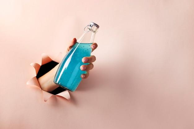 Garrafa de bebida azul brilhante com sementes de manjericão ou sementes de falooda na mão feminina através de um orifício redondo Foto Premium