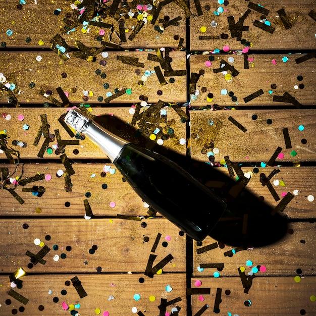 Garrafa de bebida entre confete brilhante Foto gratuita