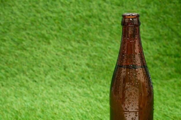 Garrafa de cerveja com grama fundo e cópia espaço Foto gratuita