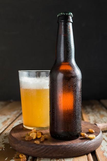 Garrafa de cerveja com nozes Foto Premium