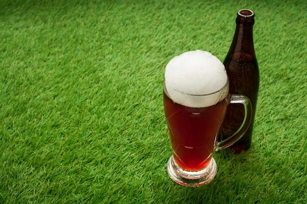 Garrafa de cerveja e copo na grama com espaço de cópia Foto gratuita