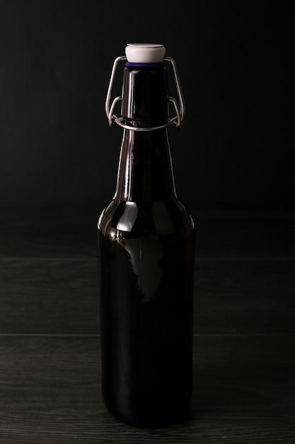 Garrafa de cerveja elegante vista frontal em fundo escuro Foto gratuita