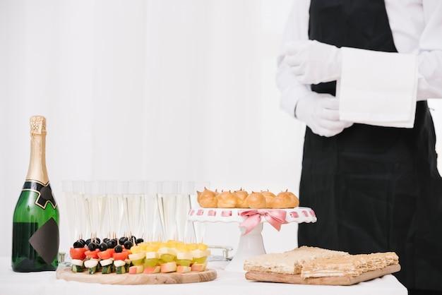 Garrafa de champanhe com comida em uma mesa Foto gratuita