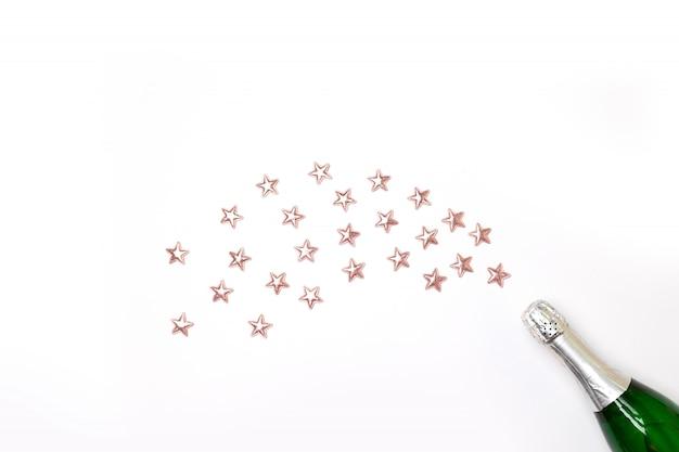 Garrafa de champanhe com estrelas de confete e flâmulas de festa em rosa Foto Premium