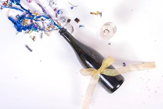 Garrafa de champanhe decorada com confete e fita Foto gratuita