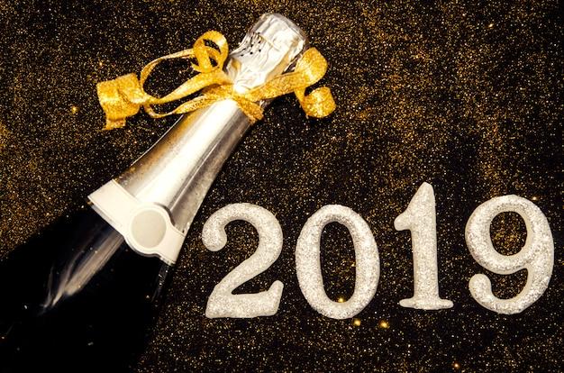 Garrafa de champanhe e números de prata 2019 em brilhos dourados em preto.feliz ano novo greeti Foto Premium